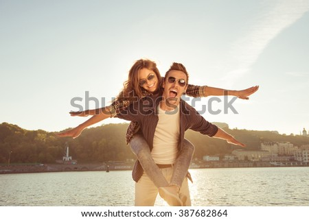 Happy man carring his gilfriend on the back at the seaside - stock photo