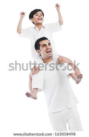 Happy man carrying his son on shoulders - stock photo