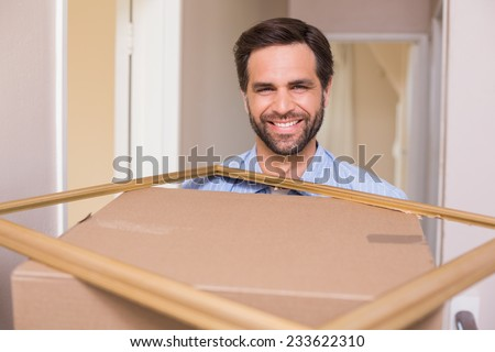 Happy man carrying moving box and frame in his new home - stock photo