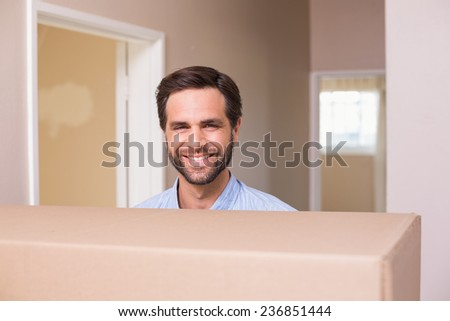 Happy man carrying moving box in his new home - stock photo