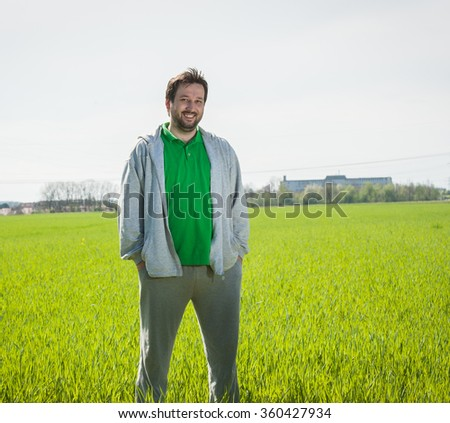 Happy man celebrating success in grass field - stock photo