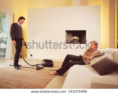 happy man cleaning the carpets in house an woman - stock photo