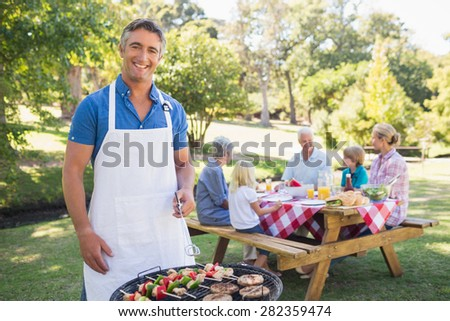 Happy man doing barbecue for his family in a sunny day - stock photo