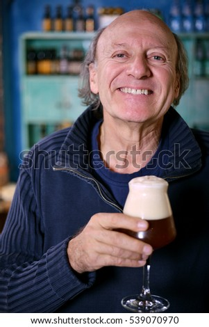 Happy man drinking a glass of beer