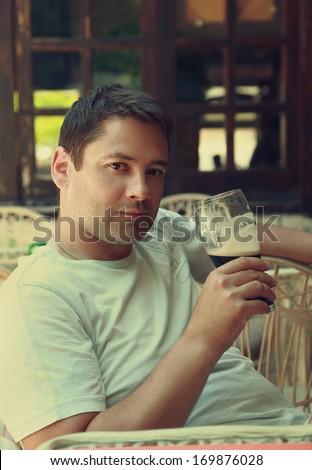 Happy man drinking dark beer in restaurant. Portrait - stock photo