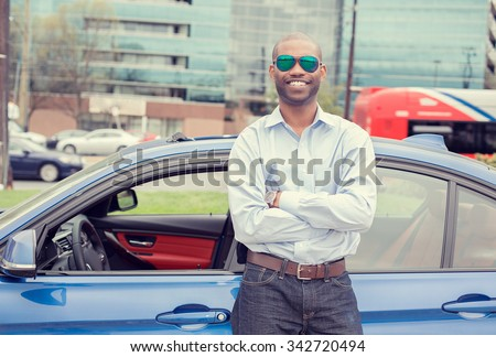 Happy man driver smiling standing by his new sport blue car isolated outside parking lot background. Handsome young man excited about his new vehicle. Positive face expression - stock photo