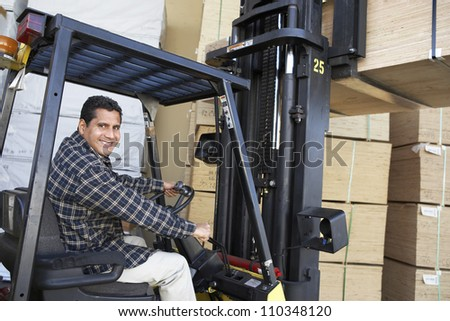 Happy man driving forklift - stock photo