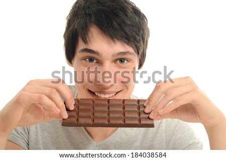 Happy man eating a yummy chocolate and having some sugar for an active day - stock photo