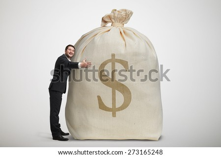 happy man embracing big bag with money over light grey background - stock photo