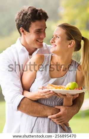 happy man embracing his beautiful girlfriend from behind  - stock photo