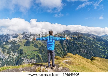 Happy man enjoying the spectacular mountain view in Swiss alps - stock photo