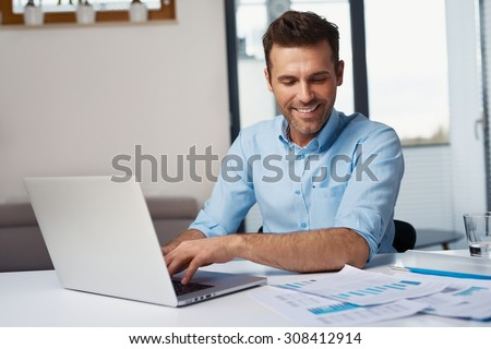 Happy man entering data from home on laptop