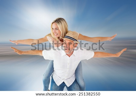 Happy man giving his partner a piggy back against room with large window looking on city - stock photo