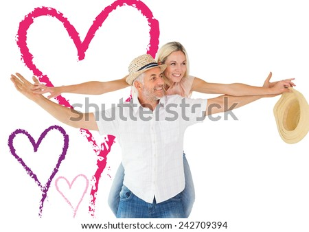 Happy man giving his partner a piggy back against valentines love hearts - stock photo