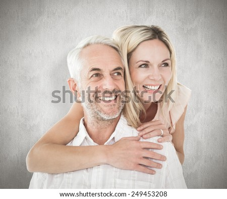 Happy man giving his partner a piggy back against weathered surface - stock photo