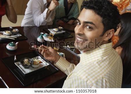 Happy man having sushi - stock photo