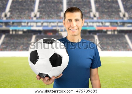 Happy man holding a soccer ball against at football stadium in background