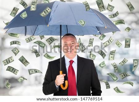 Happy man holding an umbrella in a money rain - stock photo