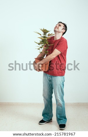 Happy man holding Cannabis plant and looking up.
