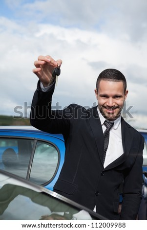 Happy man holding car keys outdoors - stock photo