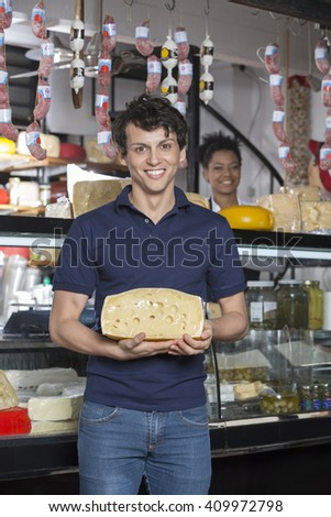 Happy Man Holding Cheese In Front Of Grocery Store - stock photo