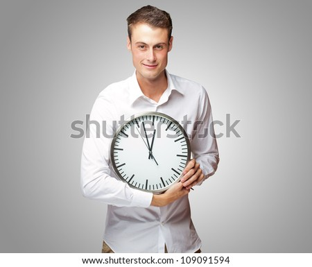 Happy Man Holding Clock In His Hand On Gray Background - stock photo