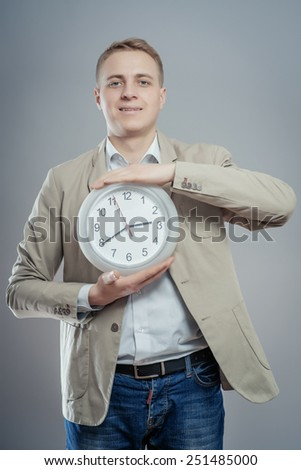Happy Man Holding Clock In His Hand On Gray Background