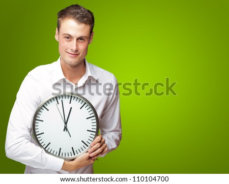 Happy Man Holding Clock In His Hand On Green Background - stock photo