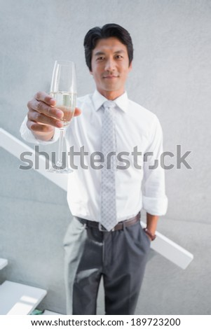 Happy man holding flute of champagne on the stairs