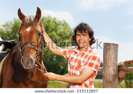 Happy man holding his beautiful horse by a bridle