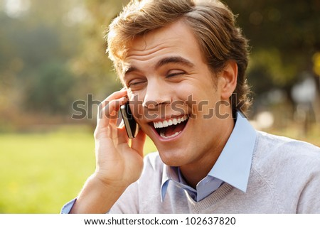 Happy man holding mobile phone outdoors - stock photo