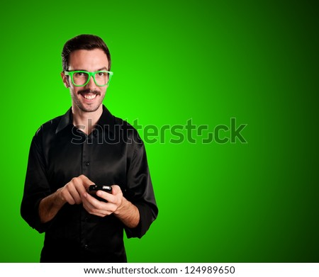 happy man holding phone on green background