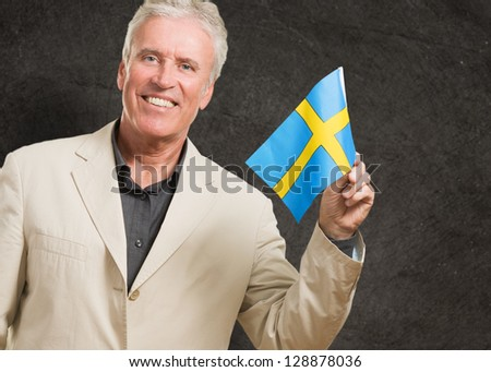 Happy Man Holding Sweden Flag against a grunge background