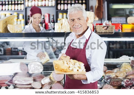 Happy Man Holding Various Cheese On Board In Store