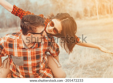 Happy man holds woman on his back, woman with flying gesture. Low contrast, with sunlight effect