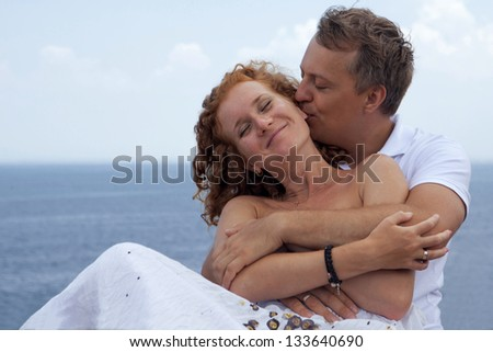 Happy man hugging his wife and kissing her ear at beach - stock photo