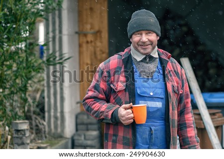 Happy Man in a knitted wool beanie, jersey and jacket standing outdoors in the snowy winter weather drinking hot coffee from a bright orange mug - stock photo