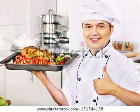 Happy man in chef hat cooking chicken. - stock photo
