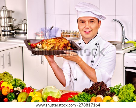 Happy man in chef hat cooking grilled chicken. - stock photo