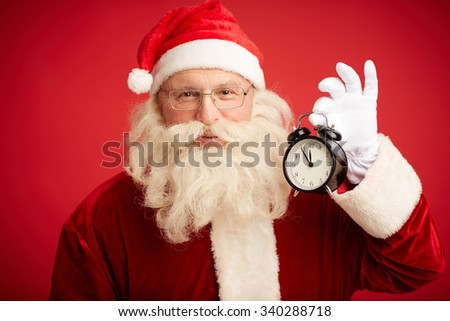Happy man in costume of Santa Claus holding alarm-clock and looking at camera - stock photo
