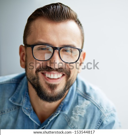 Happy man in denim shirt and eyeglasses looking at camera with toothy smile