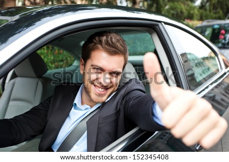Happy man in his new car - stock photo