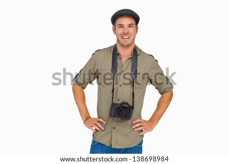 Happy man in peaked cap with camera around his neck on white background - stock photo
