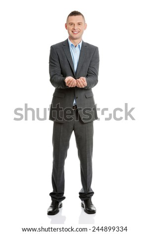 Happy man in suit showing copy space with his hand - stock photo