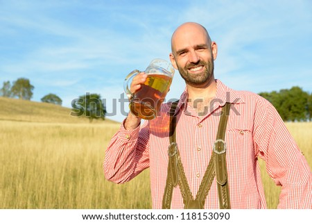 happy man in traditional bavarian garb drinks beer - stock photo