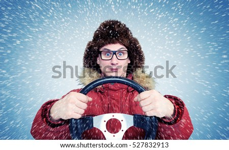 Happy Man in winter clothes with a steering wheel, snow blizzard. Concept car driver.