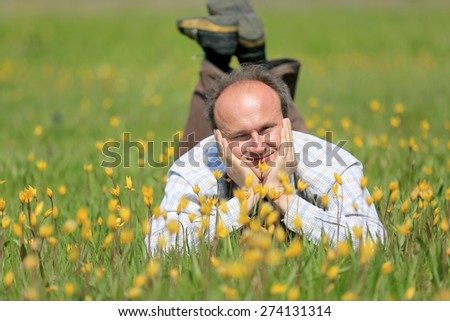 happy man in yellow wild flowers on meadow  - stock photo