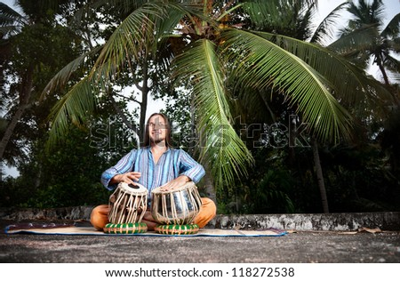 Happy man is playing on traditional Indian tabla drums at tropical palms background - stock photo