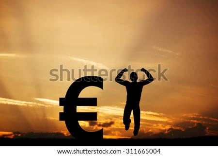 Happy man jumping for joy next to EURO symbol. Winner of lottery, financial business success concept - stock photo