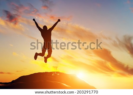 Happy man jumping for joy on the peak of the mountain, cliff at sunset. Success, winner, happiness - stock photo